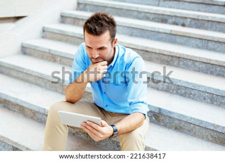 Photo of a student using a tablet and revising for his exam while sitting outdoors - stock photo