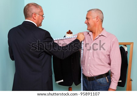 Photo of a tailor measuring a mans arm length during fitting for a new bespoke suit - stock photo