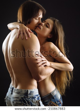 Photo of a topless young woman and man in love. - stock photo