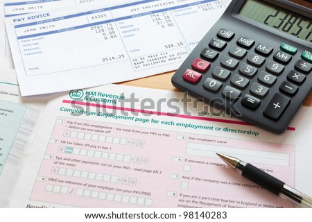 Photo of a UK self assessment tax return with calculator and payslips. The payslip is a mock up the names and all other information on it is fictional. - stock photo