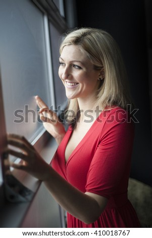 Photo of a very attractive blonde in a red dress standing by a window. - stock photo