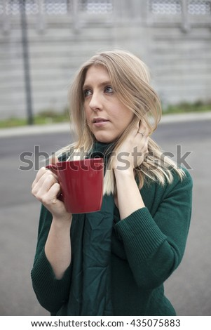 Photo of a very attractive blonde outside wearing a green top and drinking coffee from a red cup. - stock photo