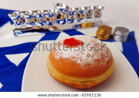 Photo of a white and blue Israeli flag with the star of David with chocolate coins, sufganiya  and silver Menora - objects for the Jewish holiday of Hanukkah. - stock photo