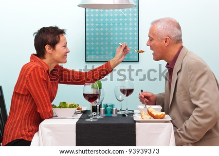 Photo of a wife letting her husband try her food in a restaurant. - stock photo