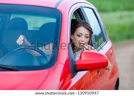 Photo of a woman applying lipstick - stock photo