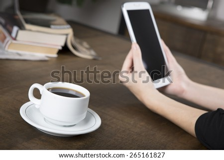 Photo of a woman holding a tablet with a no name coffee cup and a stack of books in background on a wood table with shallow depth of field - stock photo