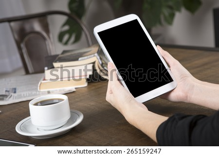 Photo of a woman holding a tablet with no name coffee cup and a stack of books in background on a wood table with shallow depth of field - stock photo