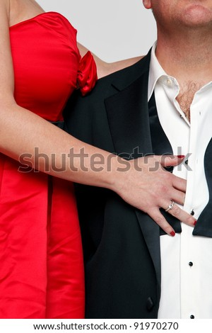 Photo of a woman in a red dress with red fingernails unbuttoning the shirt of a man wearing a tuxedo and black tie. - stock photo