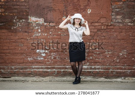 Photo of a woman in a white hat, blouse and black skirt, standing against the backdrop of an old vintage brown brick wall. Model holds the edges of the hat by hand. Woman in a retro style. - stock photo