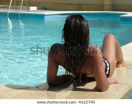 Photo of a woman lying and relaxing by a large swimming pool on holiday - stock photo