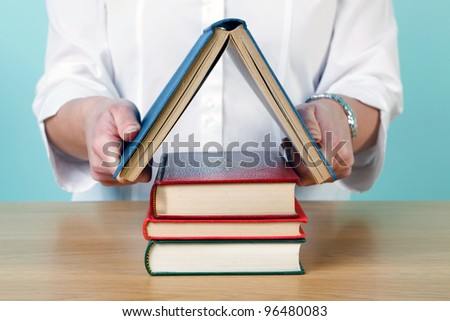 Photo of a woman making a house shape from old hardback books. - stock photo