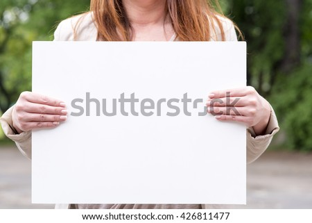photo of a woman on the outside with an empty white card - stock photo