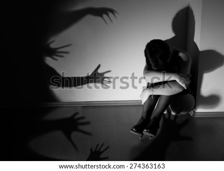 Photo of a woman who is sitting huddled on the floor sad and crying while the shadows in the shape of a hands are trying to grab her. Theme of the photo is fight against the violence against women. - stock photo