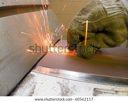 photo of a worker sanding a part and wearing protective gloves - stock photo