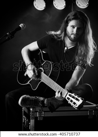 Photo of a young man with long hair and a beard playing an acoustic guitar on stage with lights and concert atmosphere. - stock photo