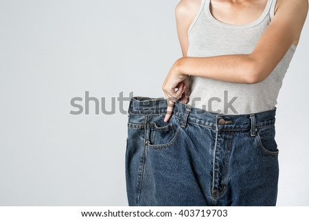 Photo of a young slim woman in oversized pair of old jeans, close up - stock photo