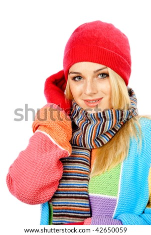 Photo of a young woman in colored sweater, gloves, touching her head with right hand against white background - stock photo