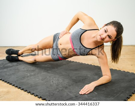 Photo of a young woman in her twenties doing a side elbow plank. - stock photo