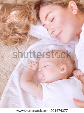 Photo of adorable newborn baby with beautiful young mother resting at home, bedtime, happy loving family, new life concept - stock photo