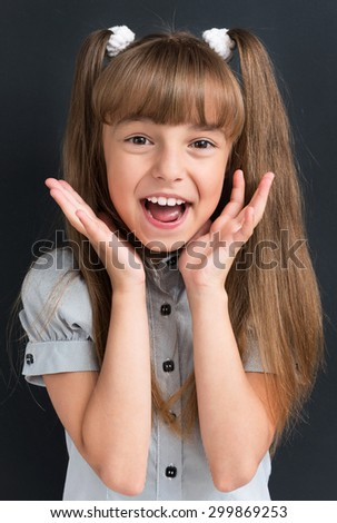 Photo of adorable young cheering girl looking at camera at the black background - stock photo
