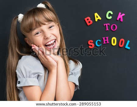 Photo of adorable young cheering girl looking at camera at the black chalkboard in classroom. - stock photo