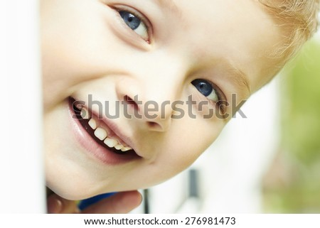 Photo of adorable young happy boy looking at camera. Outdoor face of smiling child - stock photo