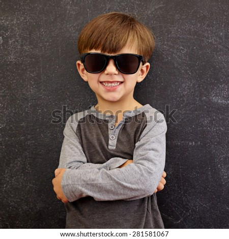 Photo of adorable young happy boy looking at camera with sunglasses. Little kid smiling with his arms crossed against black background. - stock photo