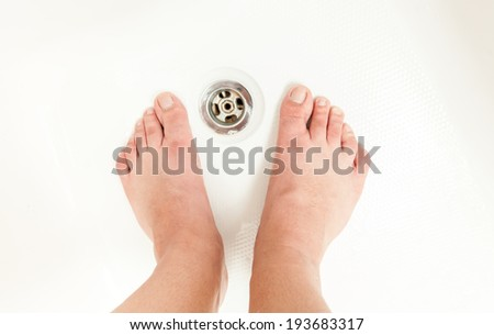 Photo of adult men feet at shower sink - stock photo