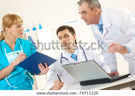 Photo of aged physician and young clinician looking at document in nurse?s hand - stock photo