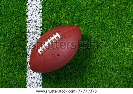 Photo of an American football on a grass next to the  touchline, shot from above. - stock photo
