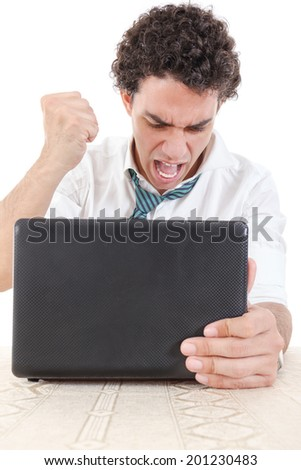 Photo of an angry and pissed off caucasian business male frustrated with work sitting in front of laptop with his hand fist hitting laptop - stock photo