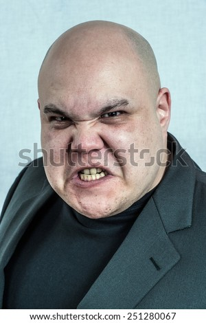 Photo of an angry bald man grimacing at the camera. Filtered to be more creepy. - stock photo