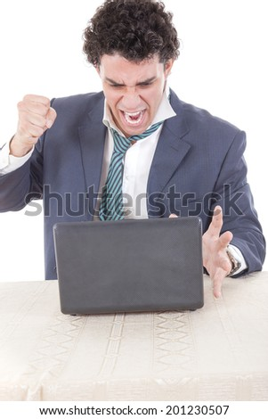 Photo of an angry caucasian business male frustrated with work sitting in front of laptop with his hand fist hitting laptop - stock photo