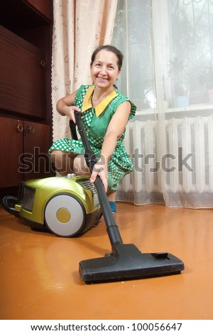 Photo of an attractive senior woman vacuuming her living room. - stock photo