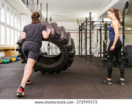Photo of an attractive young woman and man working out with a tractor tire at a gym. - stock photo