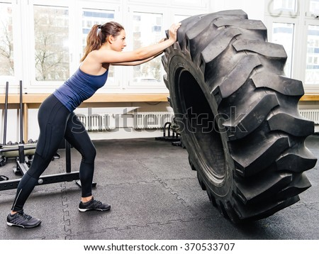 Photo of an attractive young woman working out with a tractor tire at a crossfit gym. - stock photo