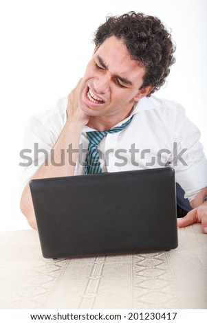 Photo of an desperate caucasian business man frustrated with work sitting in front of a laptop with his hand on neck. Stiffness, back pain and neck pain because overtime at work - stock photo