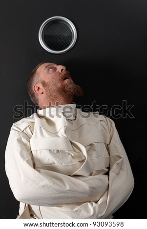 Photo of an insane man in his forties wearing a straitjacket crouched below the window of his cell. - stock photo