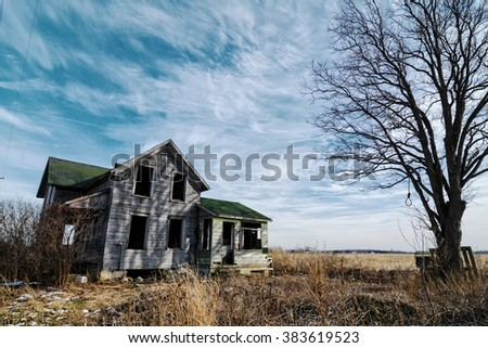 Photo of an old scary abandoned farm house that is deteriorating with time and neglect.  Enhanced with an old tree and a hangman's noose topped off with a dramatic  sky. - stock photo