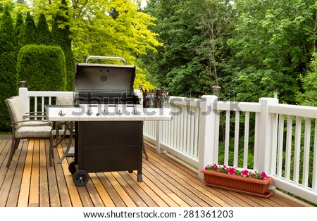 Photo of an open barbecue cooker with cold beer in bucket on cedar wooden patio. Table and colorful trees in background.  - stock photo