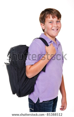 Photo of an 11 year old school boy carrying his school rucksack bag, isolated on a white background. - stock photo