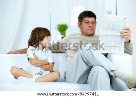 Photo of annoyed boy looking at his father reading paper at home - stock photo