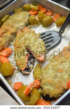 Photo of appetizing baked salmon steak in sauce baked with carrot and marrow garnish on metal baking tray - stock photo