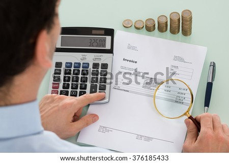 Photo Of Auditor Examining Invoice With Magnifying Glass - stock photo