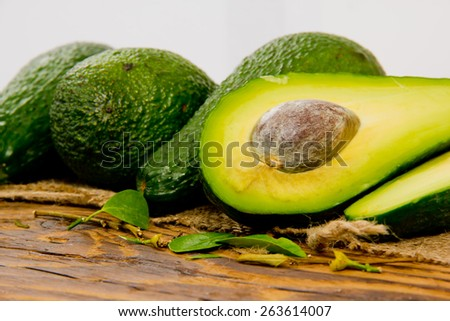 Photo of avocados with slice and leaves on burlap and wooden board - stock photo