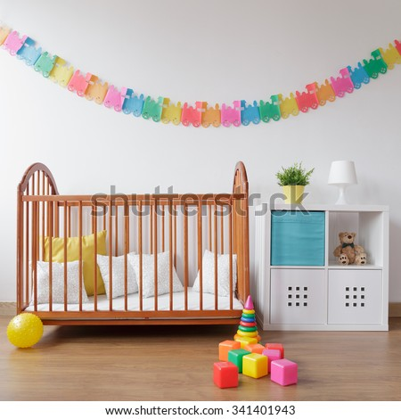 Photo of babygirl contemporary bedroom with wooden crib - stock photo