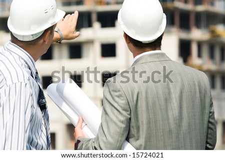Photo of backs of workers interacting and looking at building - stock photo