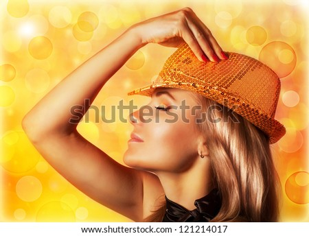 Photo of beautiful blond woman wearing stylish golden shiny hat, rear view of gorgeous female with closed eyes isolated on yellow blur background, disco club, night life, New Year party, Christmas eve - stock photo