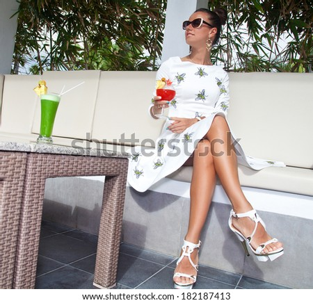 Photo of beautiful brunette woman with beautiful slim long legs sitting in a restaurant. Stylish rich girl in white dress. Glamorous lady at vacation. - stock photo