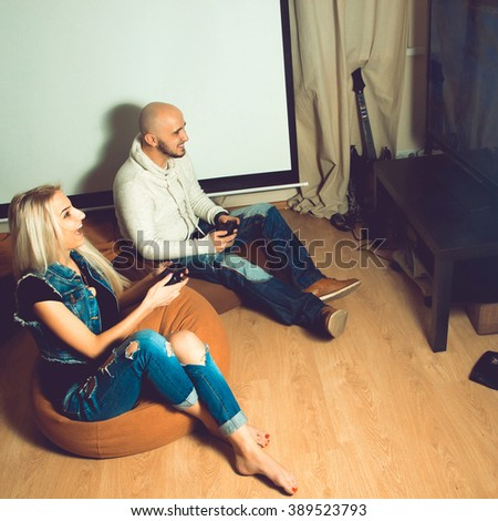 Photo of beautiful cheerful couple having fun and playing computer games. concept of leisure entertainment and fun - stock photo